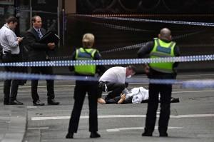 Polisi memeriksa jenazah korban penusukan di jalanan sibuk Bourke Street, Melbourne. Satu orang tewas dan dua lainnya luka-luka dalam insiden yang menurut polisi sebagai teror tersebut. AFP Photo/William West