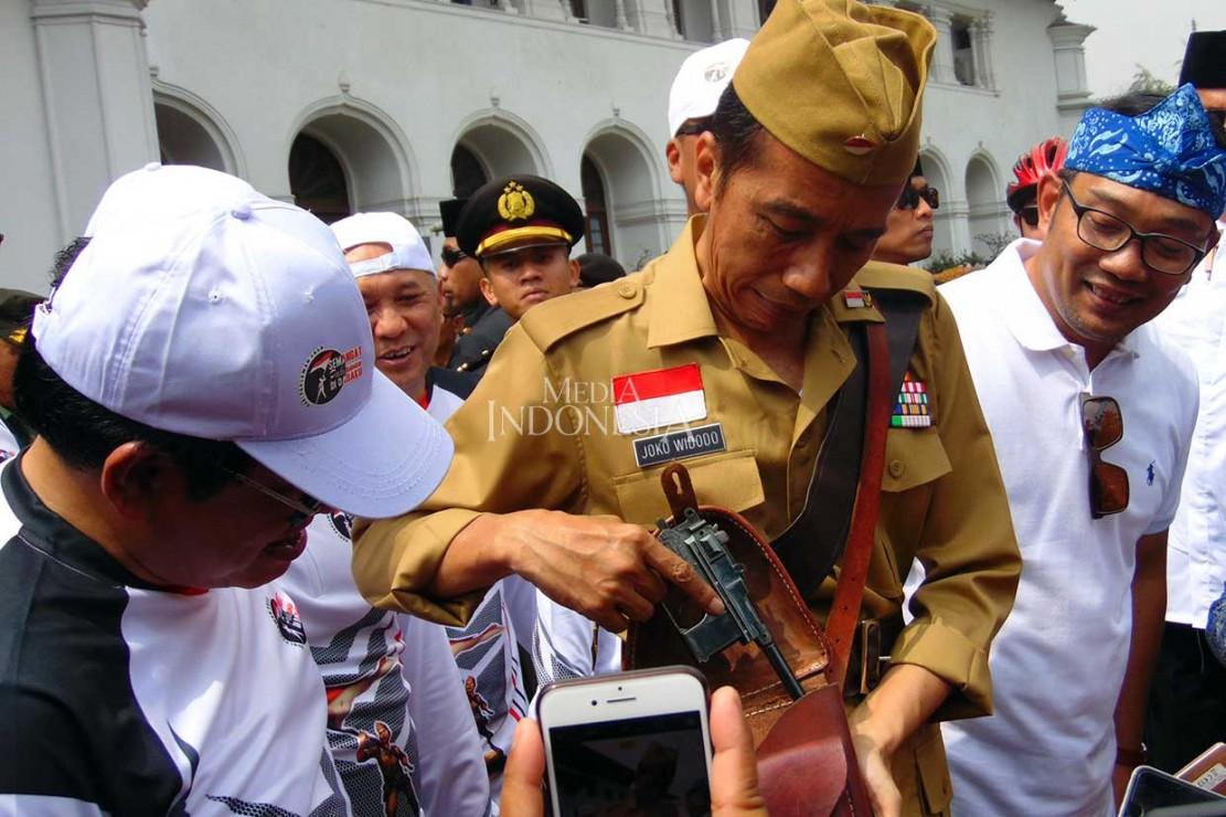 Tak hanya itu, dengan penuh canda Presiden pun menunjukkan sepucuk pistol yang digunakan sebagai atributnya saat bersepeda.