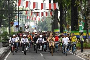 Jokowi mengenakan pakaian pejuang berwarna cokelat dan menaiki sepeda ontel berwarna hitam saat bersama sekitar 25 ribu pesepada lainnya memulai kegiatan sepeda santai. Rombongan peserta Bandung Lautan Sepeda melakukan start dari depan Gedung Sate, Jalan Diponegoro. Antara Foto/Wahyu Putro A