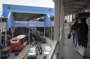Pejalan kaki melintasi Skybridge atau Jembatan Penyeberangan Multiguna (JPM) Tanah Abang di Jakarta.