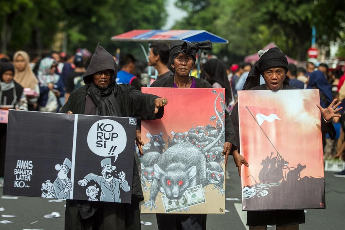 Warga membawa berbagai poster antikorupsi pada peringatan Hari Antikorupsi Sedunia di Solo, Jawa Tengah. Antara Foto/Mohammad Ayudha