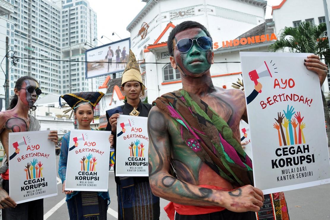 Sejumlah mahasiswa dan pelajar mengenakan pakaian adat saat menggelar peringatan Hari Antikorupsi Sedunia di Medan, Sumatera Utara. Antara Foto/Septianda Perdana