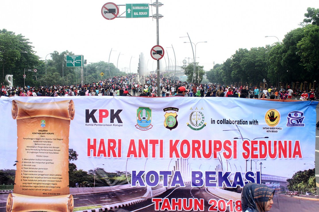 Spanduk besar membentang pada peringatan Hari Anti Korupsi Internasional di hari bebas kendaraan Jalan Ahmad Yani, Bekasi, Jawa Barat. Antara Foto/Risky Andrianto