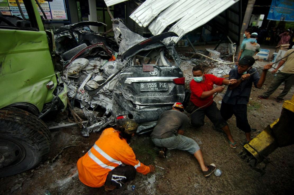 Petugas dibantu warga berusaha memindahkan mobil yang hancur terjepit truk seusai kecelakaan beruntun di jalur tengah Tegal-Purwokerto, Bumiayu, Brebes, Jawa Tengah, Senin, 10 Desember 2018.