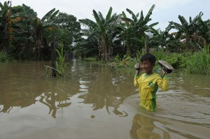 Pelajar menerobos genangan banjir luapan Sungai Batanghari di Legok, Telanaipura.
