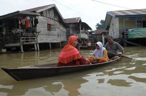 Orang tua murid menjemput anaknya menggunakan perahu dari sekolah yang tergenang banjir luapan Sungai Batanghari di Legok, Telanaipura, Jambi.