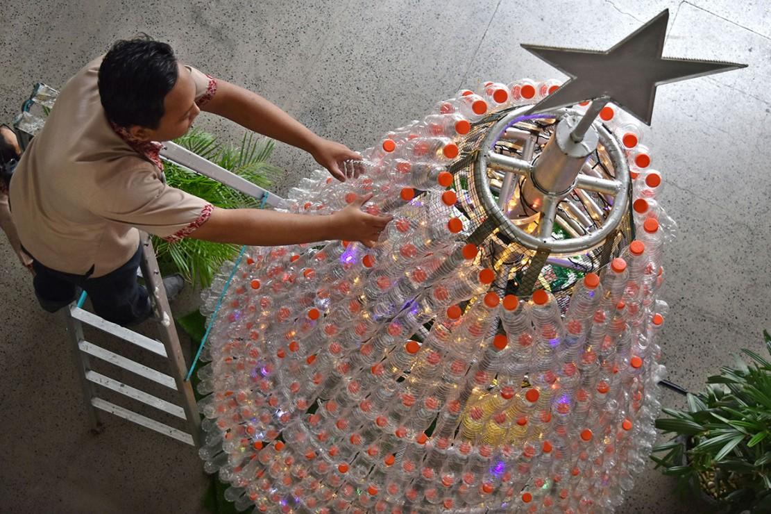 Seorang karyawan memasang botol plastik air minum dalam kemasan pada kerangka pohon natal di Hotel The Wujil, Ungaran, Kabupaten Semarang, Jawa Tengah. Antara Foto/Aditya Pradana Putra