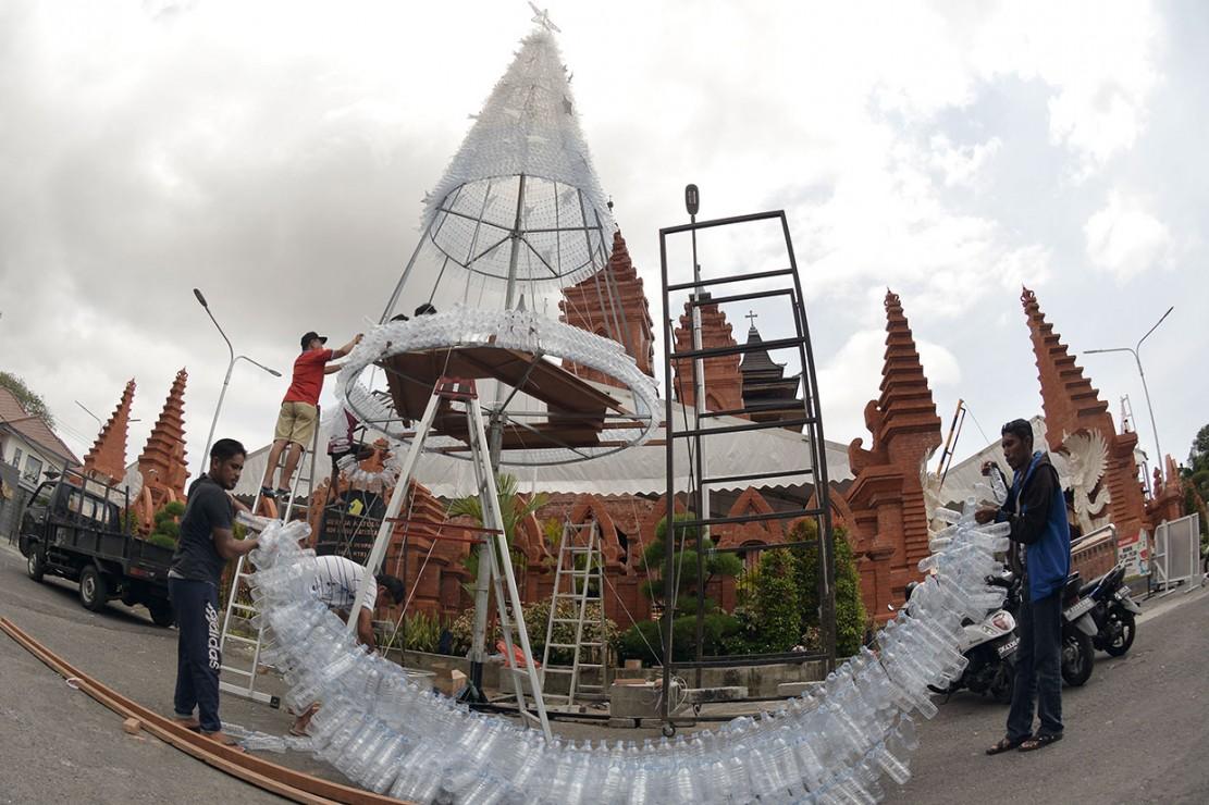 Warga membuat pohon natal dari rangkaian botol plastik bekas air mineral di Gereja Katolik Roh Kudus Katedral Denpasar, Bali. Antara Foto/Fikri Yusuf