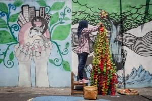 Warga menyelesaikan pembuatan instalasi pohon Natal berbahan limbah botol plastik di Purwosari, Solo, Jawa Tengah. Antara Foto/Muhammad Ayudha