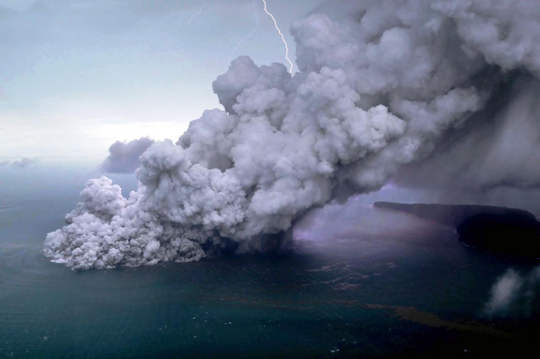 Petir dari awan badai menyambar di balik kepulan asap vulkanis yang terlontar dari kepundan Gunung Anak Krakatau.