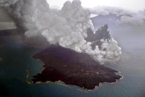 Gunung Kraakatau nampak di balik 'anaknya' yang sedang erupsi. Keduanya adalah gunung berapi aktif yang sebagian besar badannya berada di bawah permukaan laut.