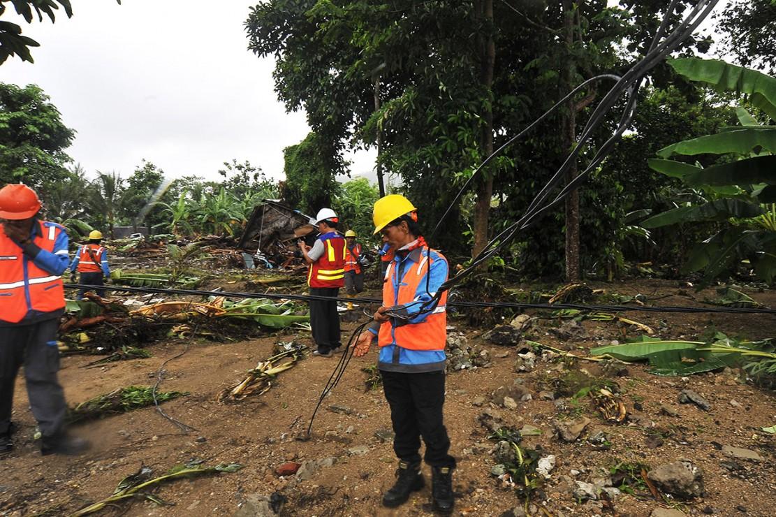 Sejumlah pekerja PT PLN membetulkan kabel jaringan listrik yang terputus akibat dihantam gelombang tsunami di Kawasan Wisata Carita, Pandeglang, Banten.