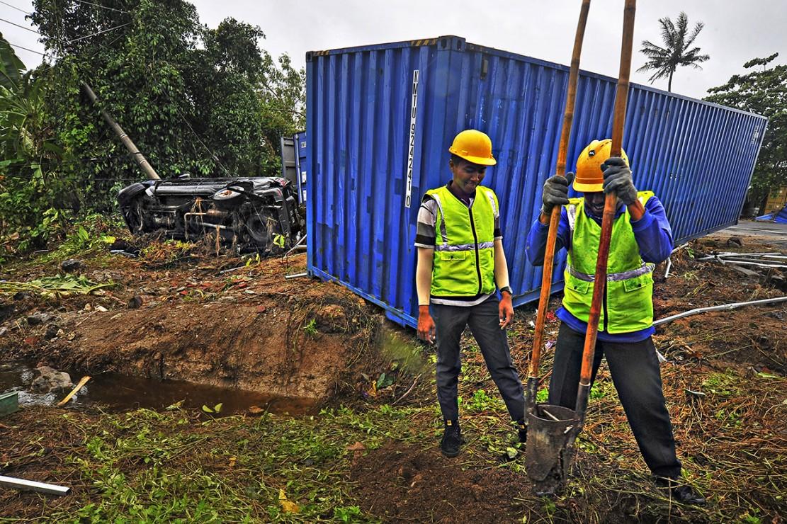 Pekerja PT PLN menggali lubang untuk menyambung kembali jaringan listrik yang terputus akibat dihantam gelombang tsunami di Kawasan Wisata Carita, Pandeglang.