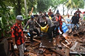 Polisi dan relawan mengevakuasi korban tewas akibat Tsunami yang tertimbun di bawah reruntuhan di kawasan Carita, Banten, Jawa Barat. Antara Foto/Akbar Nugroho Gumay