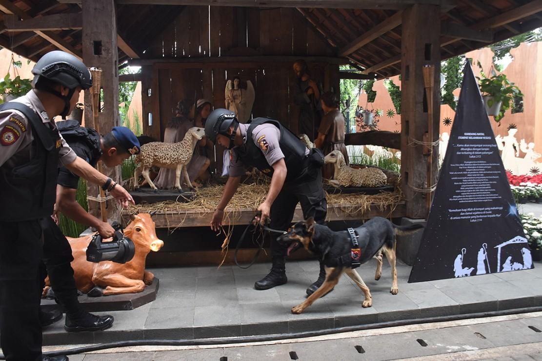 Polisi dibantu anjing pelacak melakukan sterilisasi di Gereja Katedral, Jakarta. Selain dekorasi natal, pengamanan pun diperketat. Antara Foto/Indrianto Eko Suwarso