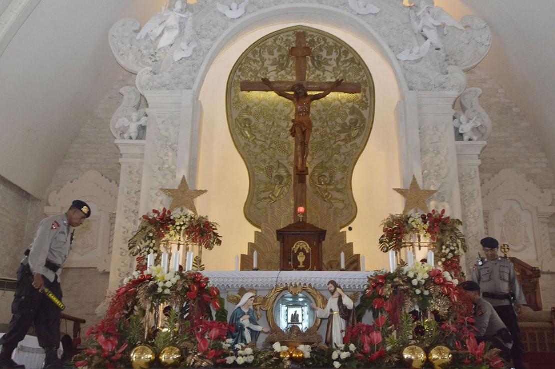 Petugas Brimob Polda Bali melakukan sterilisasi menjelang kebaktian malam Natal di Gereja Katolik Roh Kudus Katedral Denpasar, Bali. Antara Foto/Fikri Yusuf