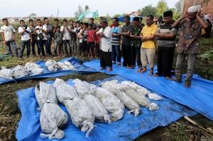 Warga menyalatkan kembali kerangka korban tsunami saat dilakukan pemindahan kuburan di Desa Kajhu, Aceh Besar, Aceh.