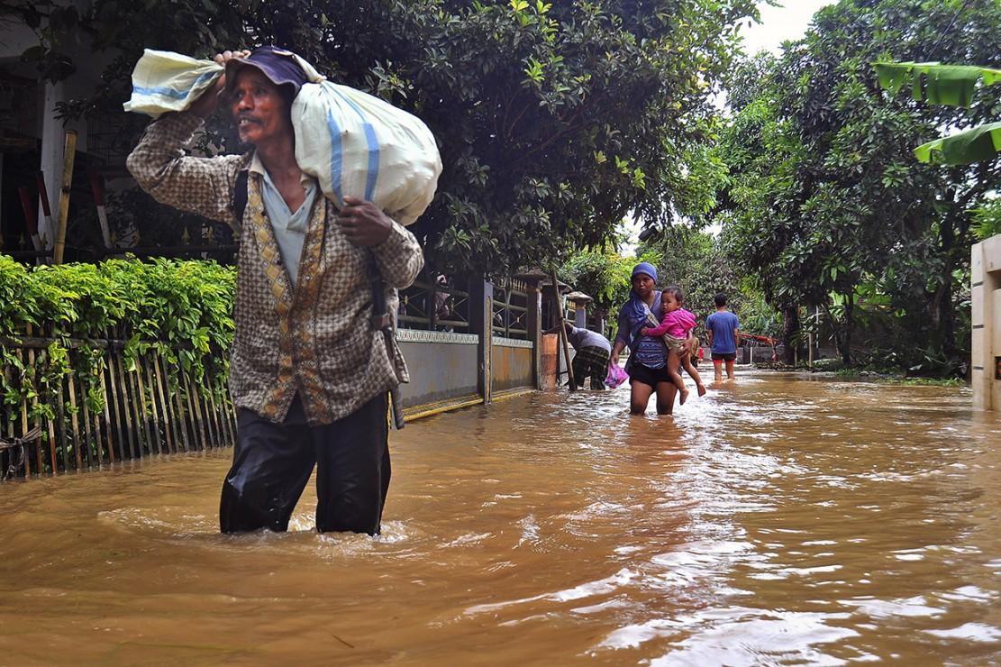 Warga melintas di jalan yang terendam banjir di Kampung Citasuk, Padarincang, Serang, Banten.