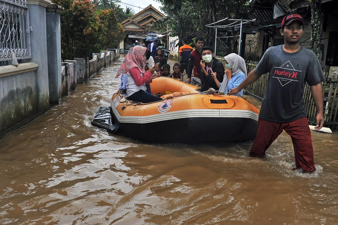 Petugas BPBD (Badan Penanggulangan Bencana Daerah) Banten mengevakuasi warga yang rumahnya terendam banjir dengan perahu karet ke tempat pengungsian sementara di Kampung Citasuk, Padarincang, Serang, Banten.