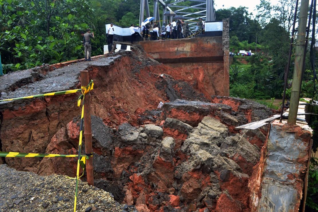 Sejumlah pejabat Pemkab Lebak meninjau badan jalan tepi jembatan yang ambles di Kampung Leuwi Jaksi, Cimarga, Lebak, Banten.