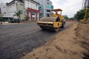 Pekerja memadatkan urukan tanah di lokasi jalan ambles di Jalan Raya Gubeng, Surabaya, Jawa Timur, Rabu, 26 Desember 2018.