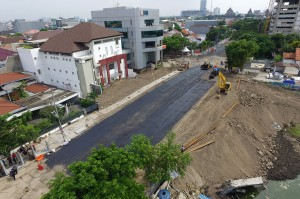 Pekerja melakukan proses 'prime coat' pada urukan tanah sebelum diaspal di lokasi jalan ambles di Jalan Raya Gubeng, Surabaya.