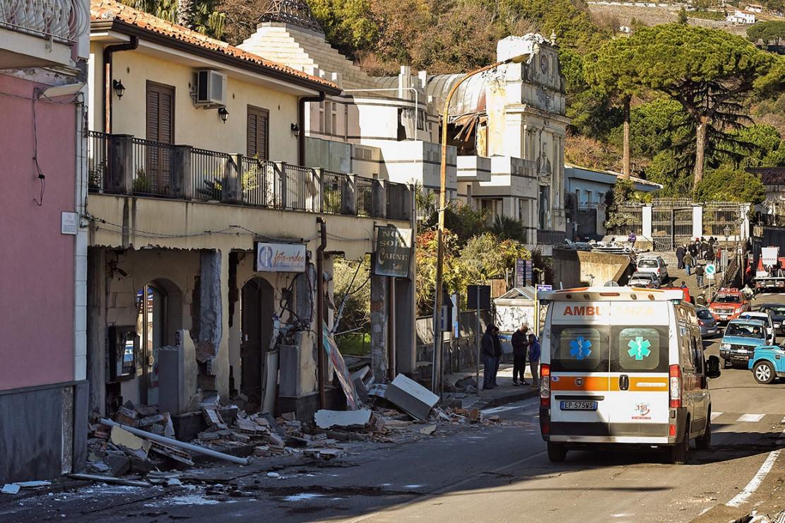Ambulans bersiaga di dekat deretan bangunan yang runtuh akibat gempa di Zafferana Etnea dekat Catania, Italia, Rabu, 26 Desember waktu setempat.