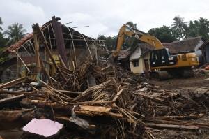 Operator alat berat membersihkan puing-puing rumah yang hancur akibat tsunami di Carita, Pandeglang, Banten. Pemerintah menyiapkan dana sebesar Rp1,98 triliun yang akan digunakan Badan Nasional Penanggulangan Bencana (BNPB) pada penanganan dampak tsunami Selat Sunda.