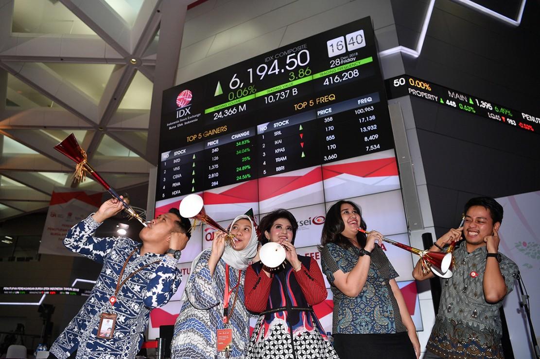Sejumlah karyawan meniup terompet saat penutupan Indeks Harga Saham Gabungan (IHSG) 2018 di kantor Bursa Efek Indonesia, Jakarta.