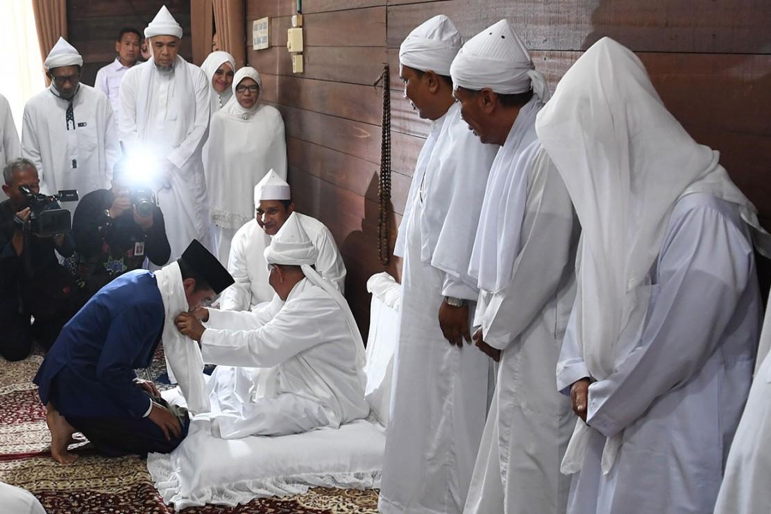 Presiden Joko Widodo menerima serban dari pengasuh Ponpes Babussalam Syekh Haji Hasyim Al-Syarwani Tuan Guru Babussalam di Langkat, Sumatra Utara, Sabtu, 29 Desember 2018.