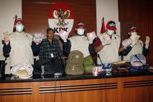 Wakil Ketua KPK Saut Situmorang (kedua kiri) menyaksikan penyidik menunjukkan barang bukti uang saat konferensi pers mengenai operasi tangkap tangan (OTT) kasus dugaan korupsi pejabat Kementerian Pekerjaan Umum dan Perumahan Rakyat (PUPR) dengan pihak swasta, di Gedung KPK, Jakarta, Minggu, 30 Desember 2018 dini hari.