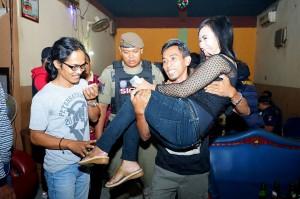 Petugas menggendong pengunjung tempat hiburan malam saat razia di Banyuwangi, Jawa Timur, Minggu, 30 Desember 2018 dini hari WIB. Antara Foto/Budi Candra Setya