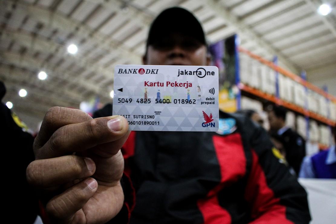 Pekerja menunjukkan Kartu Pekerja saat pendistribusian dan uji coba di Jakgrosir, Pasar Induk Kramat Jati, Jakarta.