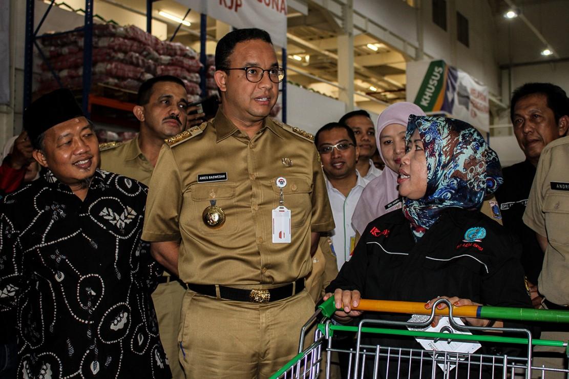 Gubernur DKI Jakarta Anies Baswedan (ketiga kiri) berbincang dengan pekerja setelah pembagian Kartu Pekerja di Jakgrosir, Pasar Induk Kramat Jati, Jakarta.