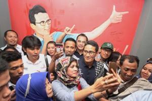 Calon Wakil Presiden nomor urut 02 Sandiaga Salahuddin Uno (tengah) melayani warga yang berswafoto di sela-sela acara peresmian Rumah Kemaslahatan Indonesia dan dialog di Surabaya, Jawa Timur.