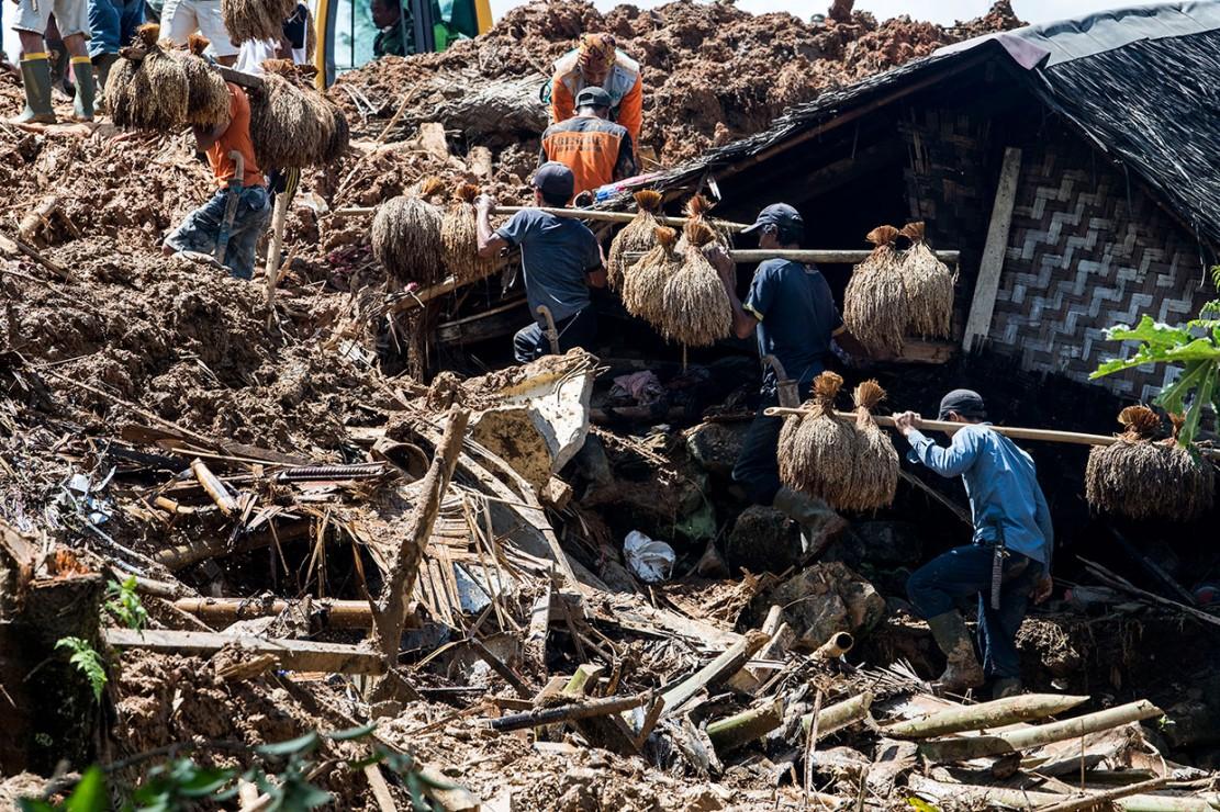 Warga bergotong-royong memindahkan padi dari lumbung yang terdampak reruntuhan tanah longsor di kampung Cimapag, Desa Sirnaresmi, Kecamatan Cisolok, Kabupaten Sukabumi, Jawa Barat, Jumat, 4 Januari 2019.