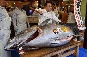 Pengusaha sushi terkenal di Jepang, Kiyoshi Kimura berpose di belakang ikan tuna sirip biru yang baru saja dia beli dalam sebuah tradisi lelang Tahun Baru di Tokyo, Sabtu, 5 Januari 2019.