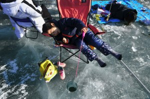 Seorang anak memancing ikan di sungai beku Hwacheon sambil bersandar di kursi, sementara pengunjung lainnya sambil tiduran.