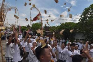 Warga saling berebut menangkap uang yang dilemparkan warga lainnya dalam tradisi Mesuryak di Desa Bongan Gede, Tabanan.
