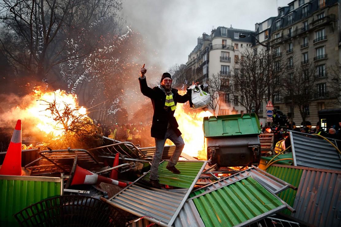 Seorang pengunjuk rasa berdiri di atas sejumlah tempat sampah yang dibakar di Paris, Prancis. Afp Photo/Abdul Abeissa