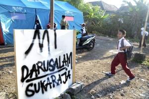 Siswa SD Yayasan Madrasah Ibtidaiyah (MI) Darussalam Sukaraja datang ke sekolah yang menggunakan tenda darurat di Desa Sukaraja, Kabupaten Lampung Selatan, Lampung.