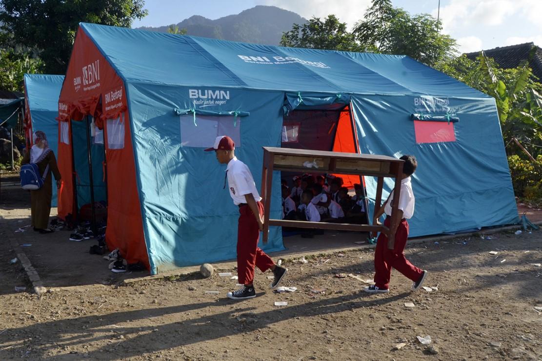 Sejumlah siswa SD Yayasan Madrasah Ibtidaiyah (MI) Darussalam Sukaraja mengangkat meja dan kursi dari sekolah mereka menuju tenda darurat untuk kegiatan belajar mengajar di Desa Sukaraja, Kabupaten Lampung Selatan, Lampung.