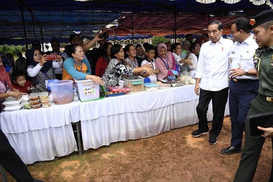 Presiden Joko Widodo didampingi Gubernur DKI Jakarta Anies Baswedan disela-sela meninjau Program Mekaar Binaan Permodalan Nasional Madani (PNM) di kawasan Tambora, Jakarta.