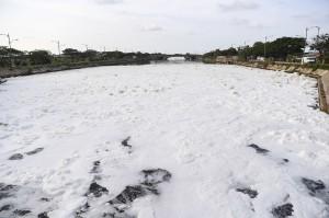 Suasana Kanal Banjir Timur yang diselimuti busa di kawasan Marunda, Jakarta.