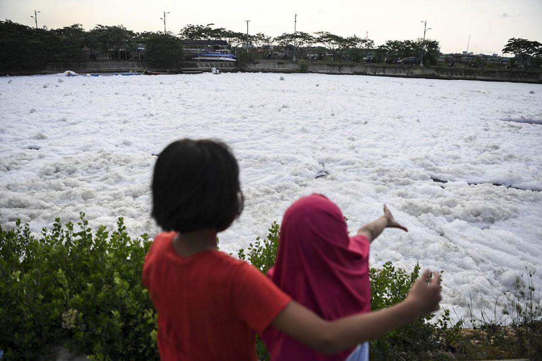 Dua orang anak melihat air Kanal Banjir Timur yang berbusa di kawasan Marunda, Jakarta.