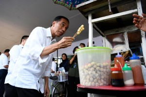 Presiden Joko Widodo membeli jajanan cilok saat meninjau usaha nasabah program pinjaman Membina Ekonomi Keluarga Sejahtera (Mekaar) binaan PNM di lapangan Sepak Bola Gongseng, Ciracas, Jakarta Timur, Kamis, 10 Jakarta 2019.