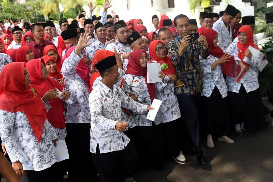 Presiden Jokowi berswafoto dengan anggota Persatuan Guru Seluruh Indonesia (PGSI) usai melakukan pertemuan.