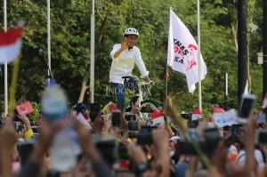 Calon Presiden pasangan nomor urut 01 Joko Widodo atau Jokowi menaiki sepeda saat ke atas panggung untuk menghadiri acara deklarasi dukungan Alumni Universitas Indonesia (UI) dan beberapa universitas negeri lainnya untuk Jokowi-Ma'ruf Amin di Kompleks Gelora Bung Karno, Jakarta, Sabtu, 13 Januari 2019.
