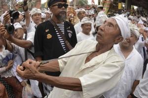 Seorang umat Hindu yang kesurupan menusukkan keris ke tubuhnya saat Tradisi Ngerebong di Pura Dalem Pengrebongan, Denpasar, Bali.