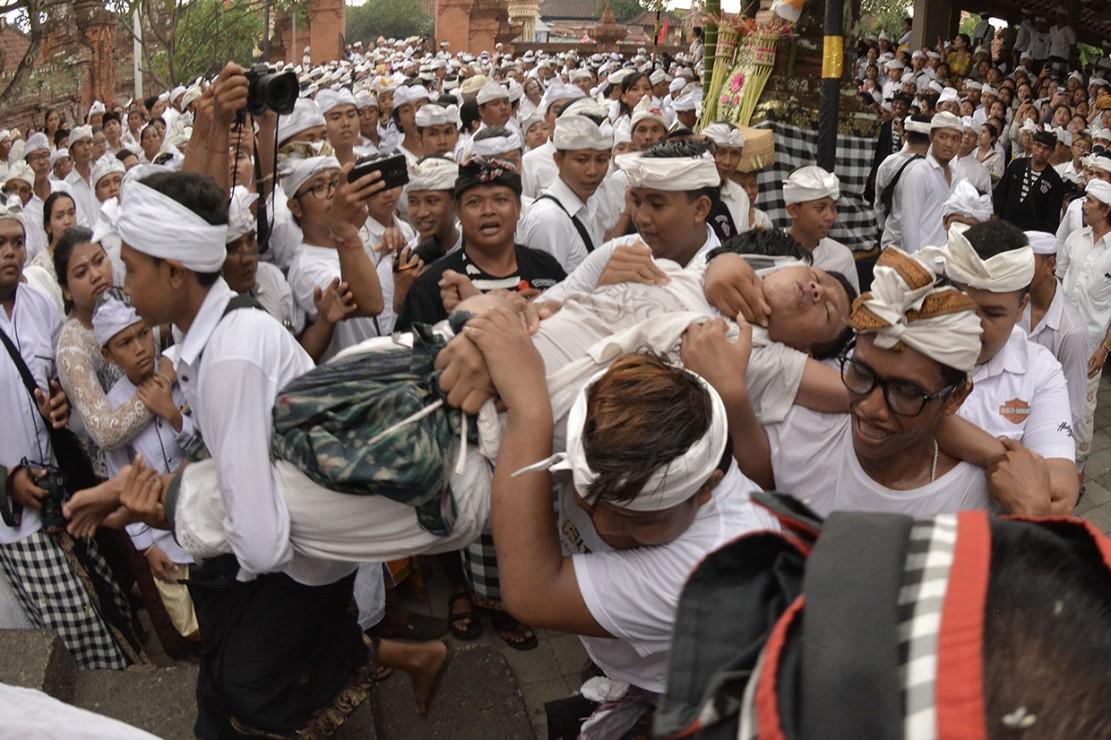 Sejumlah umat Hindu menenangkan seorang umat yang kesurupan saat Tradisi Ngerebong di Pura Dalem Pengrebongan, Denpasar, Bali.